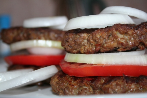 Griddled beefburgers with tomato and onion.