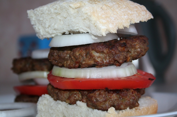 Homemade beefburgers with tomato and onion sandwiched between fresh ciabatta bread.
